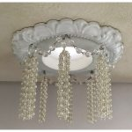 Decorative recessed light trim embellished with pearl tassels and crystal swags.